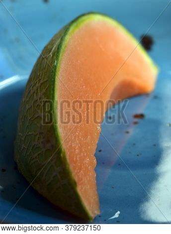 Slice Of Freshly Cut Cantaloupe Watermelon In A Blue Bowl Under Natural Light.