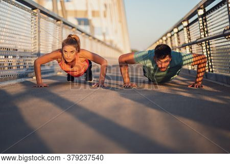 Young Couple Is Exercising Outdoor On Bridge In The City. They Are Doing Push-ups.
