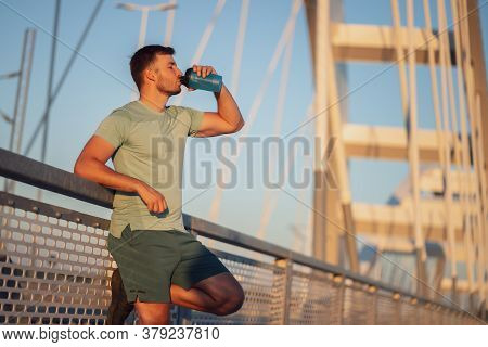 Young Man Is Exercising Outdoor On Bridge In The City. He Is Drinking Water.