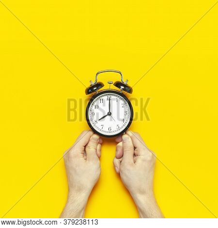 Black Vintage Alarm Clock In Male Hands On Yellow Background Flat Lay Copy Space. Retro Clock, Mecha