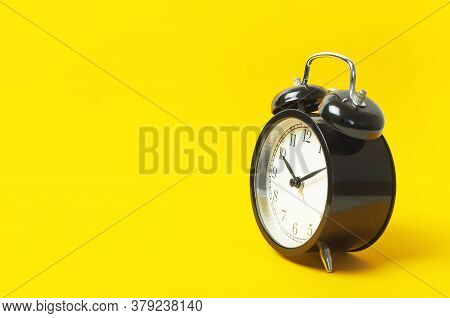 Black Vintage Alarm Clock With White Dial On Yellow Background Flat Lay Copy Space. Retro Clock, Mec