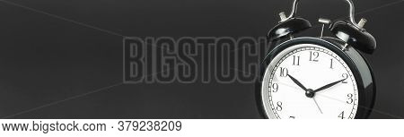 Black Vintage Alarm Clock With White Dial On Black Background Flat Lay Copy Space. Retro Clock, Mech