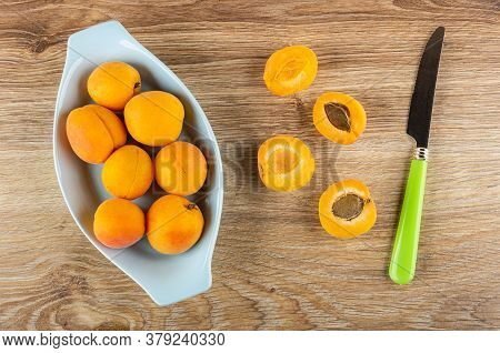 Fresh Ripe Apricots On In Pink Glass Bowl, Halves Of Apricots, Knife On Wooden Table. Top View