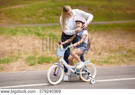 Mother Teaching Daughter To Ride Bike With Stabilisers, Putting Helmet On Her In Park Outside. Weeke