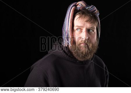 Strange Bearded Man With A Scarf On His Head. Irony And Humor On A Dark Background