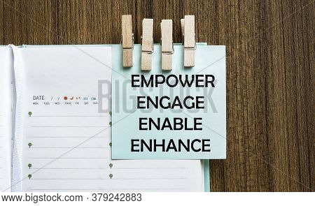 Empower Engage Enable Enhance Notes Paper And A Clothes Pegs On Wooden Background