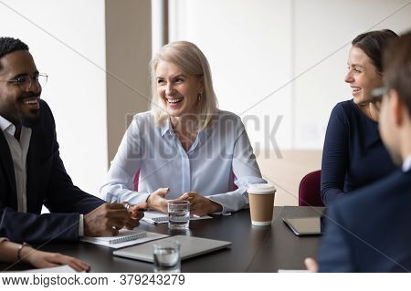 Multiethnic Cheerful Workmates Laughing During Group Briefing In Office Boardroom