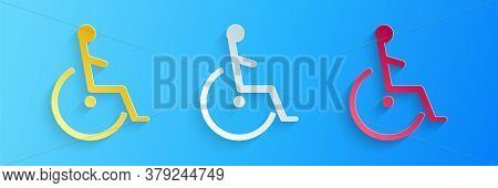 Paper Cut Disabled Handicap Icon Isolated On Blue Background. Wheelchair Handicap Sign. Paper Art St