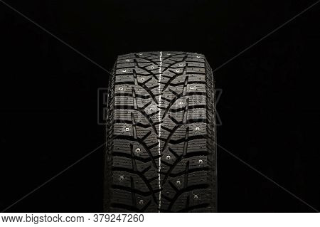 Studded Winter Tire, Front View, Close-up On A Black Background