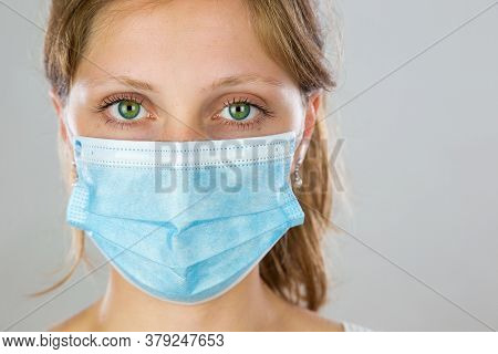 Young Woman With Green Eyes Wearing Blue Surgical Face Mask And Facing Camera.