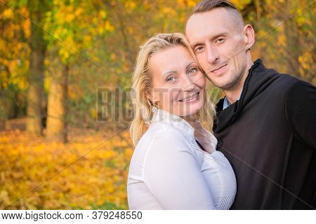 Lovely Middle-aged Couple In Autumn Park. Smiling Man And Woman Hugged On Fall Background. Couple Ha