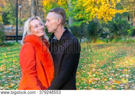 Middle-aged Couple In Autumn Park. Smiling Pair On Colorful Fall Background. Lovely Couple On Autumn