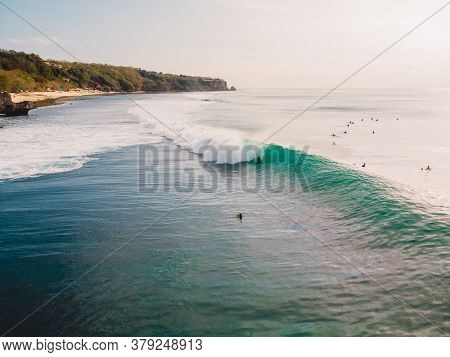 Aerial View Of Surfer At Barrel Wave. Blue Perfect Waves And Surfers In Ocean