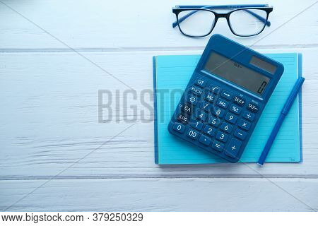 Close Up Of Blue Calculator And Notepad On Color Background