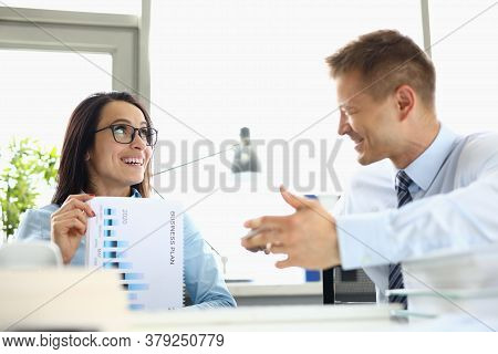 Businesswoman Smiling And Holding Business Plan Her Colleague Laughing And Gesturing With Her Hands.