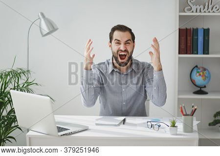 Irritated Bearded Business Man In Gray Shirt Sit At Desk Work On Laptop Pc Computer In Light Office