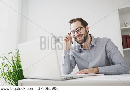 Smiling Young Bearded Business Man In Gray Shirt Glasses Sitting At Desk In Light Office On White Wa