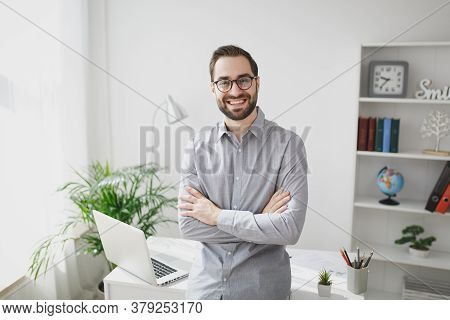 Smiling Young Bearded Business Man In Gray Shirt Glasses Standing Near Desk With Laptop Computer In