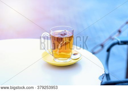 Tea On White Table Sea Port Background , Warm Tone. Tea Bags In Glass On A Restaurant In The Port Ne