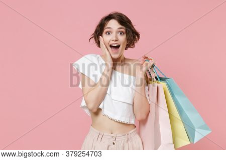 Excited Young Woman Girl In Summer Clothes Hold Package Bag With Purchases Isolated On Pastel Pink B