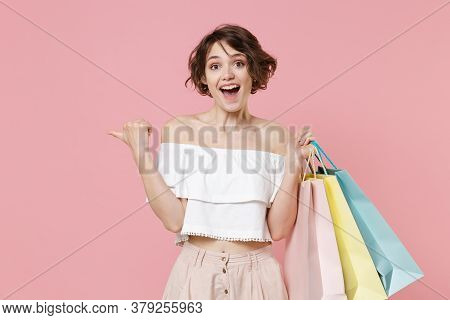 Excited Young Woman Girl In Summer Clothes Hold Package Bag With Purchases Isolated On Pink Wall Bac