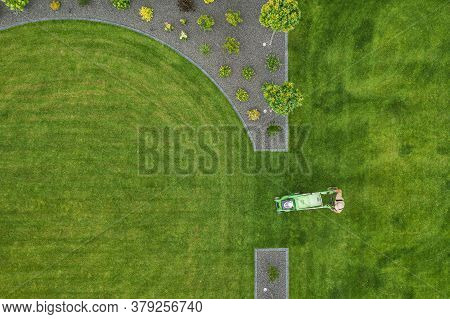 Caucasian Landscaping Worker Trimming Backyard Grass Using Electric Mower. Gardening And Landscaping