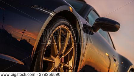 Scenic Sunset Reflection In Supercar Body. Sporty Looking Vehicle With Large Golden Alloy Wheels. Au