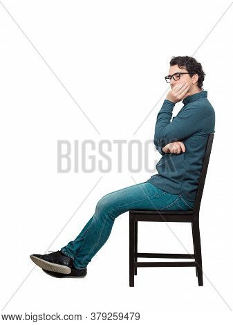 Side View Full Length Annoyed Businessman Sitting On Chair, Keeps Hand Under Cheek, Makes Displeased