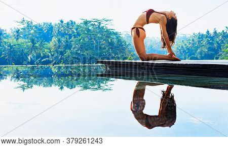Stretching On Sunrise Background. Active Woman In Bikini Practicing Yoga At Villa Poolside To Keep F