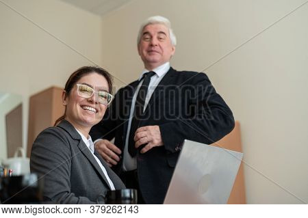 A Mature Male Boss Praises A Subordinate. A Woman In A Suit Works At A Laptop At A Desk. Friendly Co