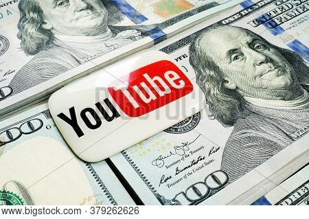 Kyiv, Ukraine - July 30, 2020: Youtube Logo Lies On The Wads Of Money. Earnings By Video Blogging.