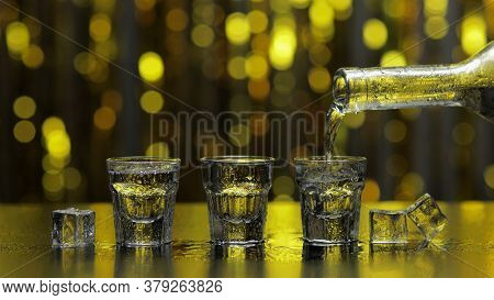 Bartender Pouring Up Frozen Vodka From Bottle Into Three Shots Glasses With Ice Cubes Against Shiny