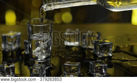 Bartender Pouring Up Frozen Vodka From Bottle Into Shot Glass With Ice Cubes Against Shiny Gold Part