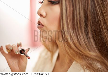 A Young Beautiful Asian Woman In A Beige Lace Dressing Gown Put On Morning Makeup And Puts Lipstick