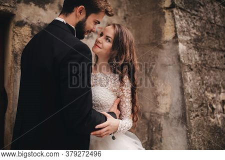 Happy Newlywed Couple Hugging And Kissing In Old European Town Street, Gorgeous Bride In White Weddi