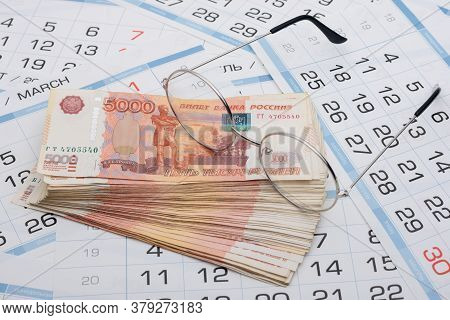 Glasses Lie On A Bundle Of Five-thousandth Russian Banknotes, Background From Calendar Sheets