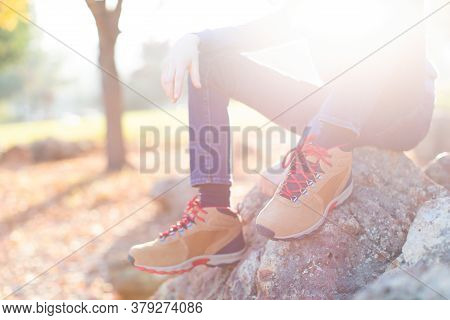 Close-up View Of Boy's Legs In Trekking Boots, Child Sitting On A Rock With No Face Visible Due To S