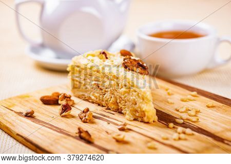 Napoleon Cake With Different Nuts On Wooden Board