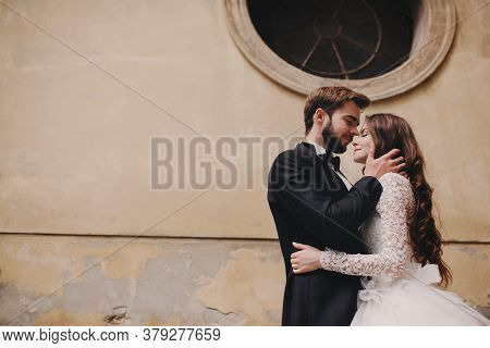 Stylish Bride And Groom Gently Hugging In European City Street. Gorgeous Wedding Couple Of Newlyweds