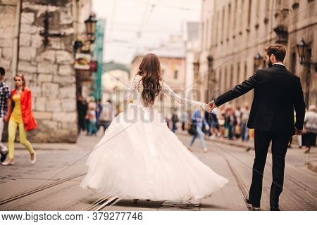 Happy Newlyweds Couple On A Walk In Old European Town Street, Gorgeous Bride In White Wedding Dress