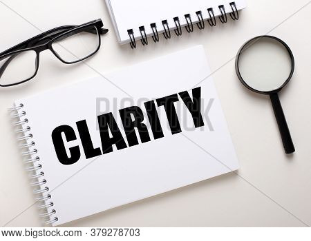 The Word Clarity Is Written In A White Notebook On A White Background Near A Black Magnifier And Bla