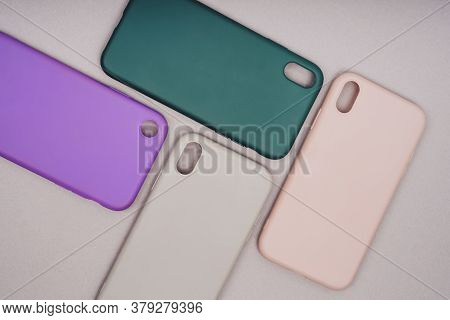 A Few Silicone Cases For The Smartphone. The Phone Is In A Gray Case. Purple, Grey, Green And Pink S