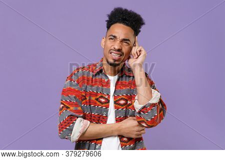 Puzzled Tired Young African American Guy In Casual Colorful Shirt Posing Isolated On Violet Wall Bac