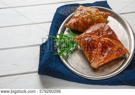 Homemade Pastries With Meat And Sauce With Rosemary Served On A Metal Tray On White Wooden Table