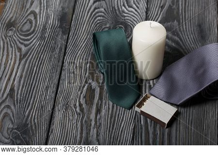 A Man's Ties And A Large White Candle. Beside A Box Of Matches. Love And Togetherness Objects. On Pa