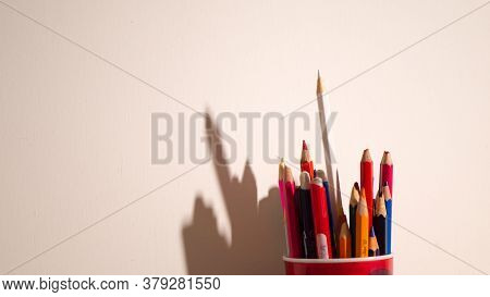 Colorful Pencils In Red Glass On A White Background With Stark Shadows.