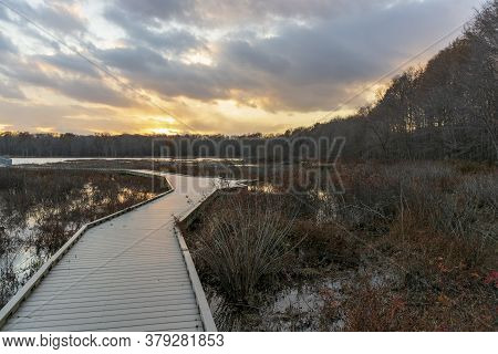 A Wooden Boardwalk Winds Through A Barren Marshland While A Wonderful Display Of Colors Dance Across