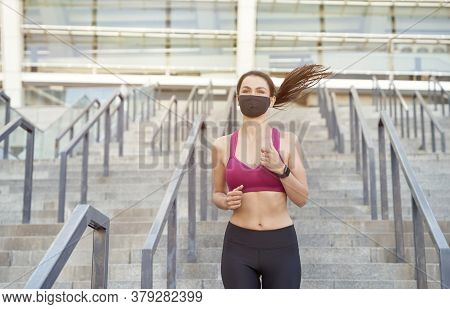 Running Safely During The Outbreak. Young Athletic Woman In Sport Clothes Wearing Protective Face Ma