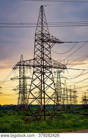Electricity Pylons Bearing The Power Supply Across A Rural Landscape During Sunset. Selective Focus.