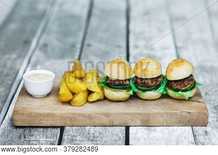 Three Mini Burgers With Beef Patty, French Fries And Mayonnaise On Wooden Board. Shabby Aged Table B